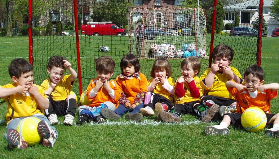 Little kids making faces on soccer field
