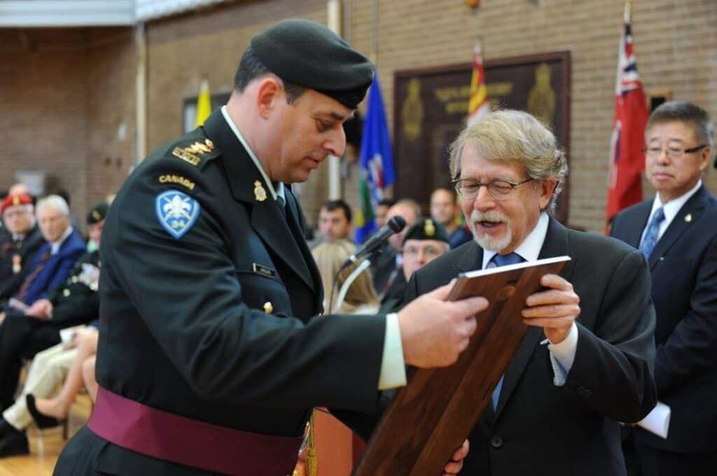 """Le maire, Bill Steinberg, présente la plaque """"Freedom of the City"""" remise au lieutenant-colonel sortant, Paul Langlais, lors de la cérémonie de passation de commandement, dimanche 25 octobre 2015."""