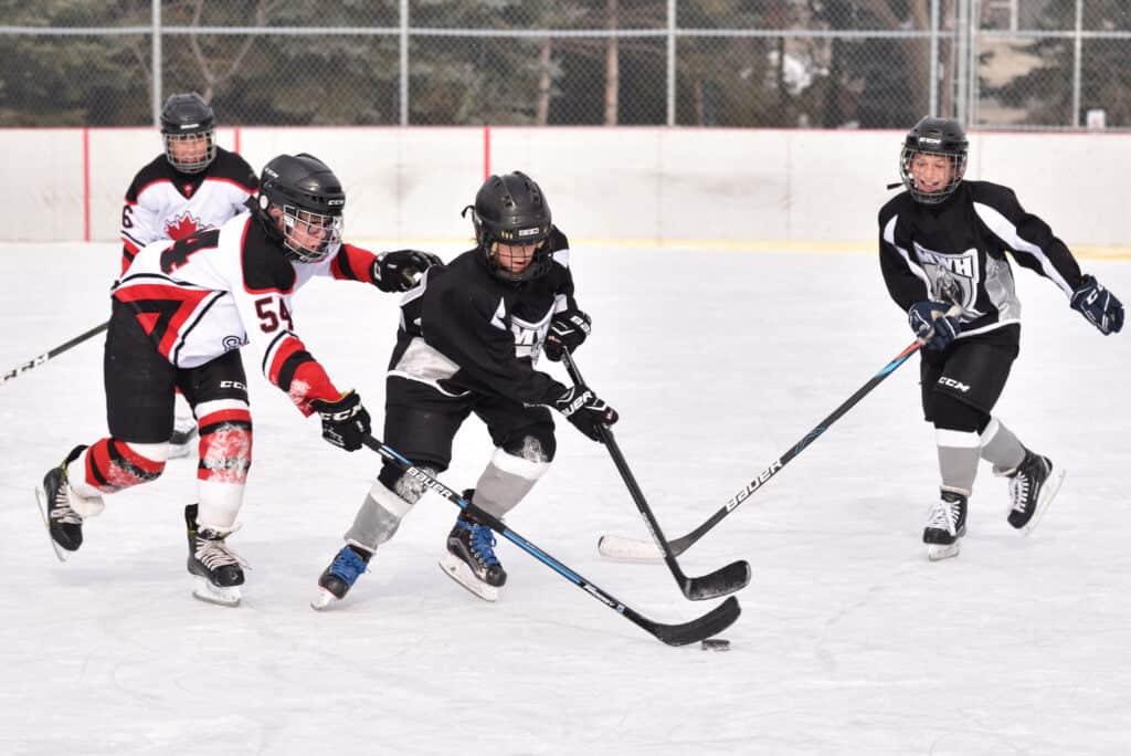 des enfants jouant au hockey sur une patinoire extérieure